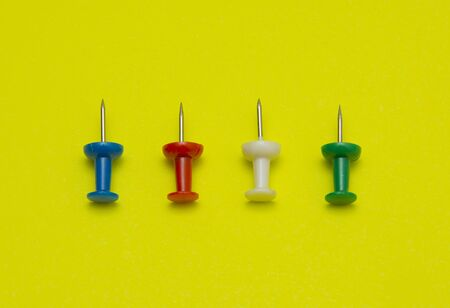 yellow tacks: Set of push pins in different colors, isolated on yellow background.