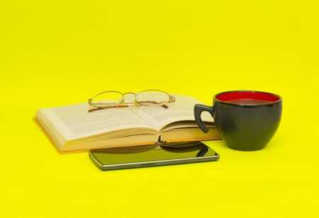 wold: Cup of coffee with book isolated on yellow background Stock Photo