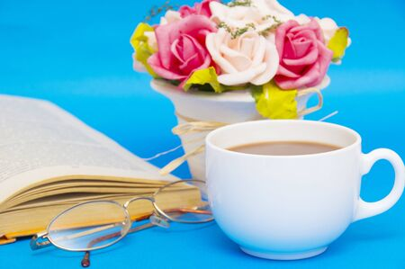 living wisdom: Cup of coffee with book isolated on blue background