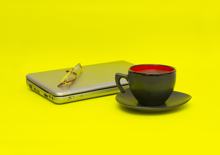 wold: Cup of coffee with computer isolated on yellow background Stock Photo