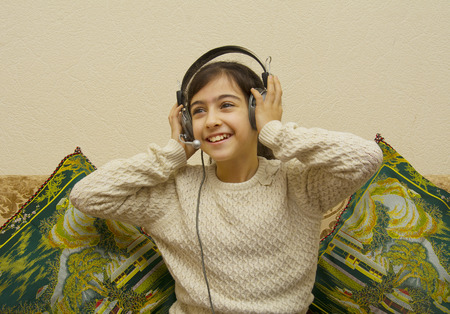 Girl listening music in headphones while sitting on sofa in room Stock Photo