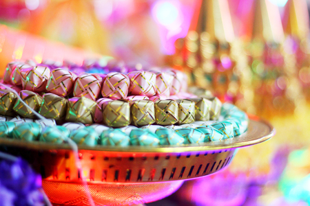 ordination: coins in colorful ribbin in a gold bowl for Newly ordained Buddhist monks given in charity