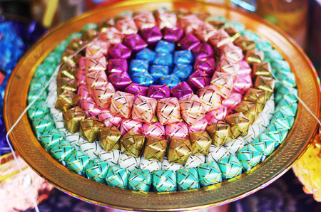 ribbin: coins in colorful ribbin in a gold bowl for Newly ordained Buddhist monks given in charity