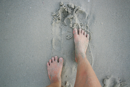 beach feet: wide angle shot of a pair of feet standing on a sandy beach, feet on the beach - Sand texture