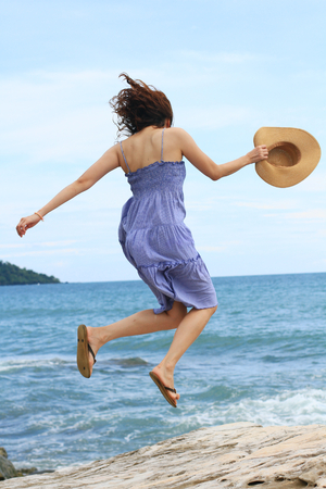 lengthy: Happy young beautiful woman jumping on the beach