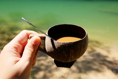 The Morning coffee in the glass from natural coconut shells on woman hands