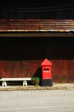 Red Postbox on footpath near old wooden house at countryside In Thailand