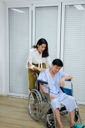 Thai woman is Caring and Take the old father sitting on wheelchair and ill health for to see a doctor at hospital in Thailand Banque d'images