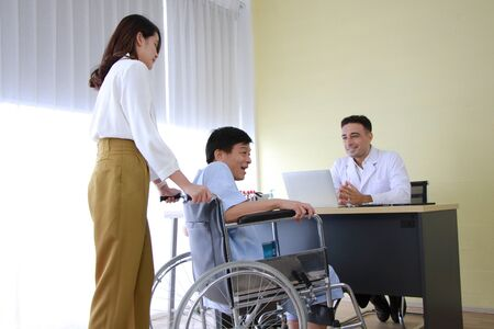 Thai woman is Caring and Take the old father sitting on wheelchair and illness health for to see a doctor at hospital in Thailand Banque d'images