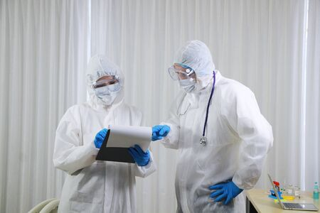 Medical team in Personal Protective Equipment or PPE clothing and Researching and Discussing for patients infected with the Covid 19 virus and treatment in lab of hospital in Thailand