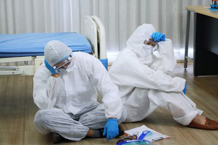 Medical team in Personal Protective Equipment or PPE cloth sitting and so tried after treat patients infected with the Covid 19 virus and treatment in lab of hospital in Thailand