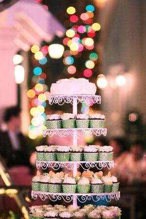 Cupcakes de mariage avec des paillettes colorées dans une tasse verte avec fond de bokeh de lumières de guirlande