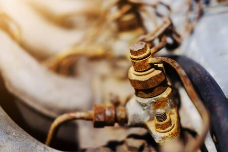 Old Rustic knot and rusty iron chains knotted with sunlight on engine of motor car  版權商用圖片