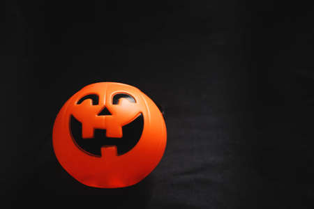 Smiling Halloween pumpkin head on black clothes in natural shadow and sunlight. Halloween holiday concept. Foto de archivo