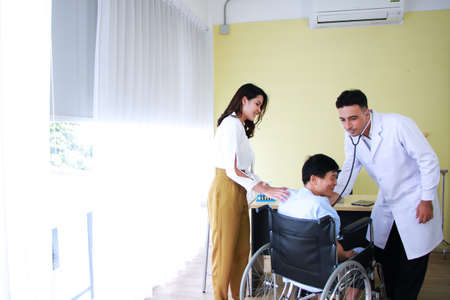 Thai woman is Caring and Take the old father sitting on wheelchair and illness health for to see a doctor and Checked by Stethoscope at hospital in Thailand Imagens
