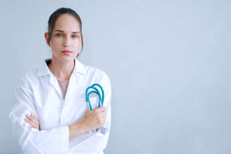 Beautiful caucasian doctor woman in Gown uniform and hand holding stethoscope is smiling portrait on white wall background.