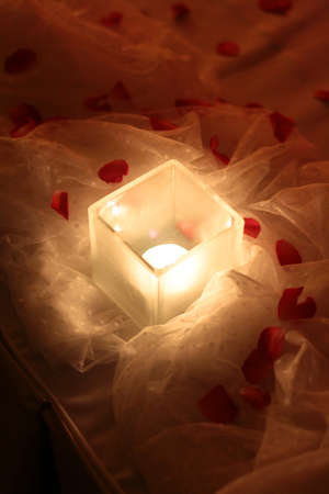 Candle light and red roses petals decoration on white cloth for wedding and valentine day Archivio Fotografico