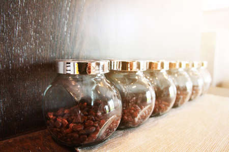 Coffee beans in glass bottles on wooden shelf with sunlight in the kithcen.Coffee shop