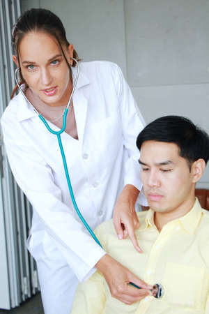 Professional Caucasian Psychiatrist (MD) woman is checking heart wave by Stethscope with young asian man. Major depressive disorder patients and healthcare Concept.