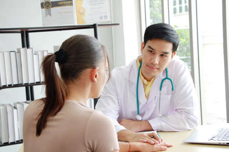Professional Asian man Psychiatrist (MD) is counseling and Hold hands for treament young caucasian woman. Major depressive disorder patients and healthcare Concept.