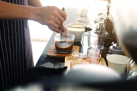 Asian barista young man making coffee according to order at counter bar with natural sunlight in the morning in modern cafe and restaurants.