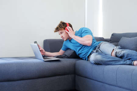 Young Caucasian man listening to musice by headphone and searching online social media with laptop. He islying on sofa in living room. Lifestyle with techonology on holiday Concept.