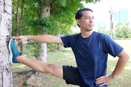 Smiling Asian man is exercising and stretching the legs to relax the muscles after running and jogging in the garden of city. Sport and healthy Concept