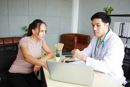 Young Asian male psychiatrist is specialist in psychiatry Caucasain female Patient serious together for therapy and talking for encourage with laptop in Clinical treatment for emotional symptoms. Archivio Fotografico