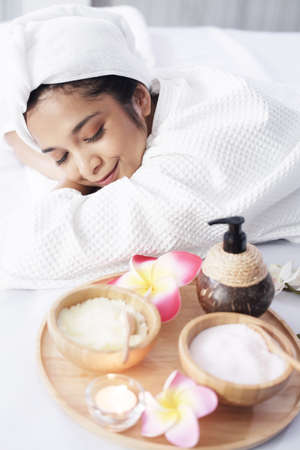 Smiling Asian woman in white headscarf and bath towel lie down and relaxing on bed preparing for massage therapy at alternative medicine healing spa Center in Th