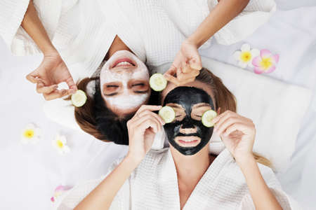 Smiling Caucasian and Asian two girls friends is holding Sliced ​​cucumber and relaxing with facial masks for skine care on white bed together. Beauty salon and lifestyle of lesbian Concept.