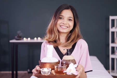 Smiling Professional Asian Thai Massage therapist woman is ้holding a herbals tray for therapy at alternative medicine healing spa Center in Thailand.