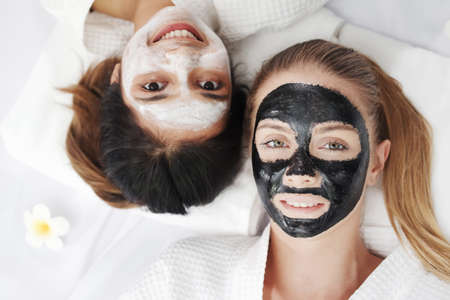Caucasian and Asian two girls friends is smiling and relaxing with facial masks for skine care on white bed together at massage therapy spa. Beauty salon and lifestyle of lesbian Concept. 免版税图像