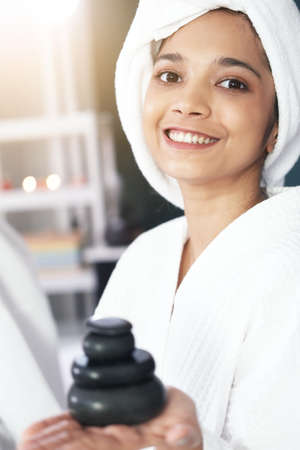 Asian woman in bath towel is smiling and hand holding Natural stone healing in therapy spa and beauty salon. 免版税图像