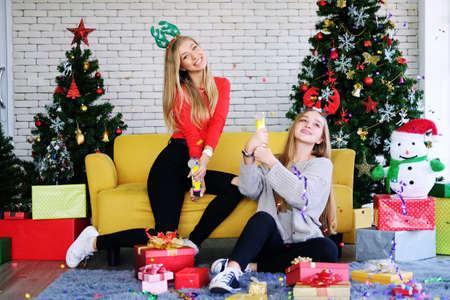 Caucasian girls friends funny with confetti Paper fireworks in christmas time and celebrating new year eve party. Lifestyle of Lesbian on holiday Concept