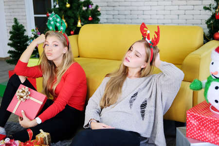 Caucasian couple girls friends sitting on the floor and holding big Gift boxes in Christmas party. They are drunk. Life style of on holiday concept. Stock Photo