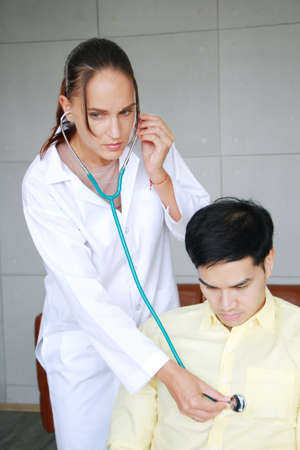 Professional Caucasian Psychiatrist woman is checking heart wave by Stethscope with young asian man. Major depressive disorder patients and healthcare Concept.