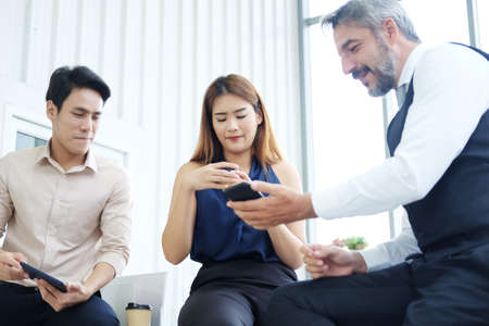 Smiling Asian team and Senior Caucasian boss is businesspeople teamwork relaxing and brainstorm. Businesswoman holding coffee glass and talking about smartphone at office. Focus at Asian woman