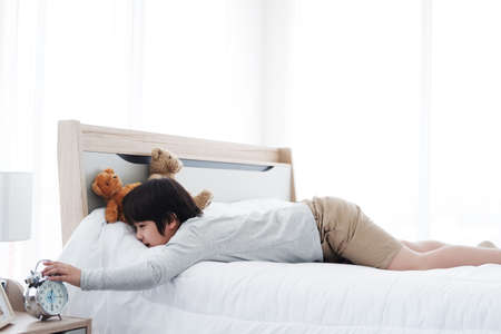 Asian boy wake up late and turn off the alarm on the bed in the morning and lazy to go to school.