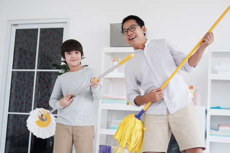 Smiling asian father and little boy child is enjoying for House cleaning together in Laundry room.