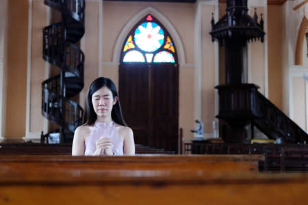Asian woman is sitting on wooden chair and Praying to god in a Christian church for make a wish for hope and encouragement in life. Rituals and beliefs in Christian of Thailand concept.