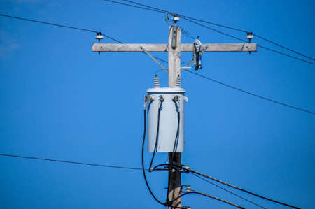 Energy and technology: electrical post by the road with power line cables, transformers and phone lines against bright blue sky Stock Photo - 18089374