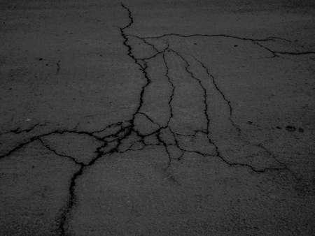 ひびの入ったアスファルト路面の暗いテクスチャ