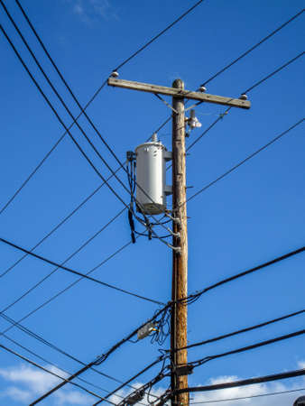 telephone pole: Transformers of an electrical post with powerlines against