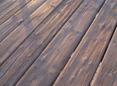 Wooden Boardwalk - This picture is of a boardwalk constructed of strong timber wood that overlooks the ocean waves near a beach; the wood reflects a strong resistance to the ocean salt overspray as it serves as a sturdy walking path for visitors