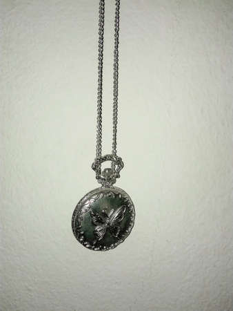 Silver pocket watch vintage style with butterfly cover is hung on the wall. Standard-Bild