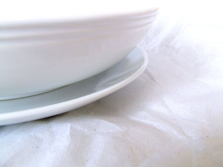 some ceramic and porcellin clean white plates and bowls, wrapped in or laying on clean white tissue paper