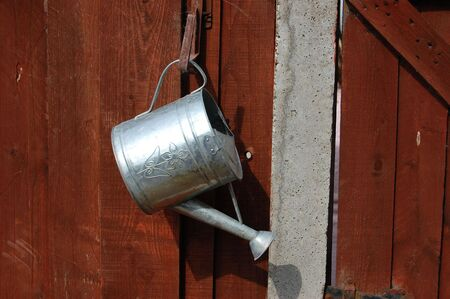 a metal watering can hanging up on wood fence