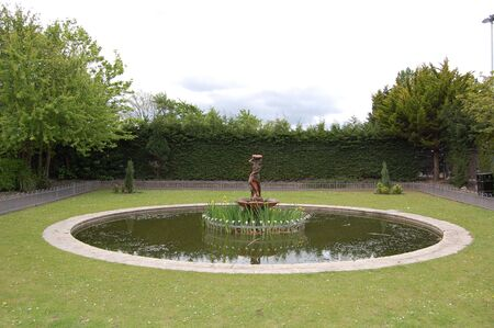 a small pond water feature with bushes and statue