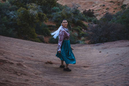 Native American Woman in Traditional Dress on Sandstone