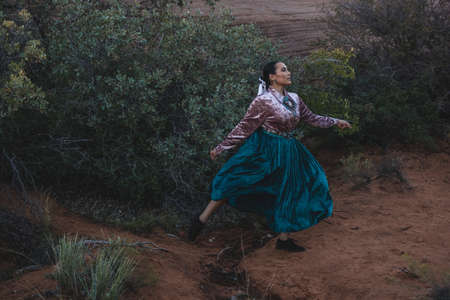 Native American Woman near large Sage Brush in Arizona Desert